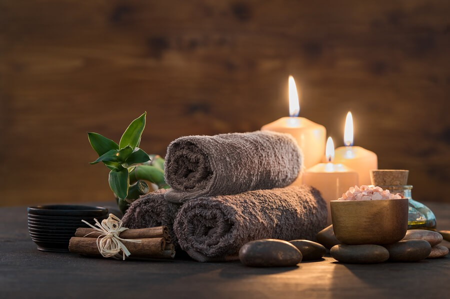 relaxing towels and candles next to a plant
