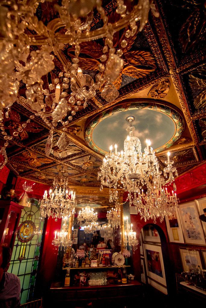 an 18th century look, chandeliers handing from deep velvet reds pairs with a sea blue door, the gothic era