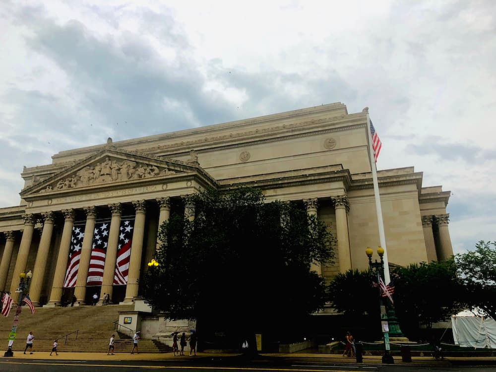 the sun was setting upon the national archives that evening, and the flag's bright red vibrance hued through the eve.