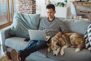 A man enjoying apartment life on his couch with his dog.
