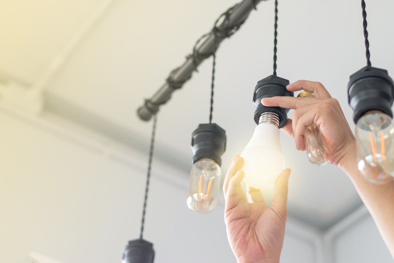 An apartment tenant installing smart LED light bulbs in her apartment.