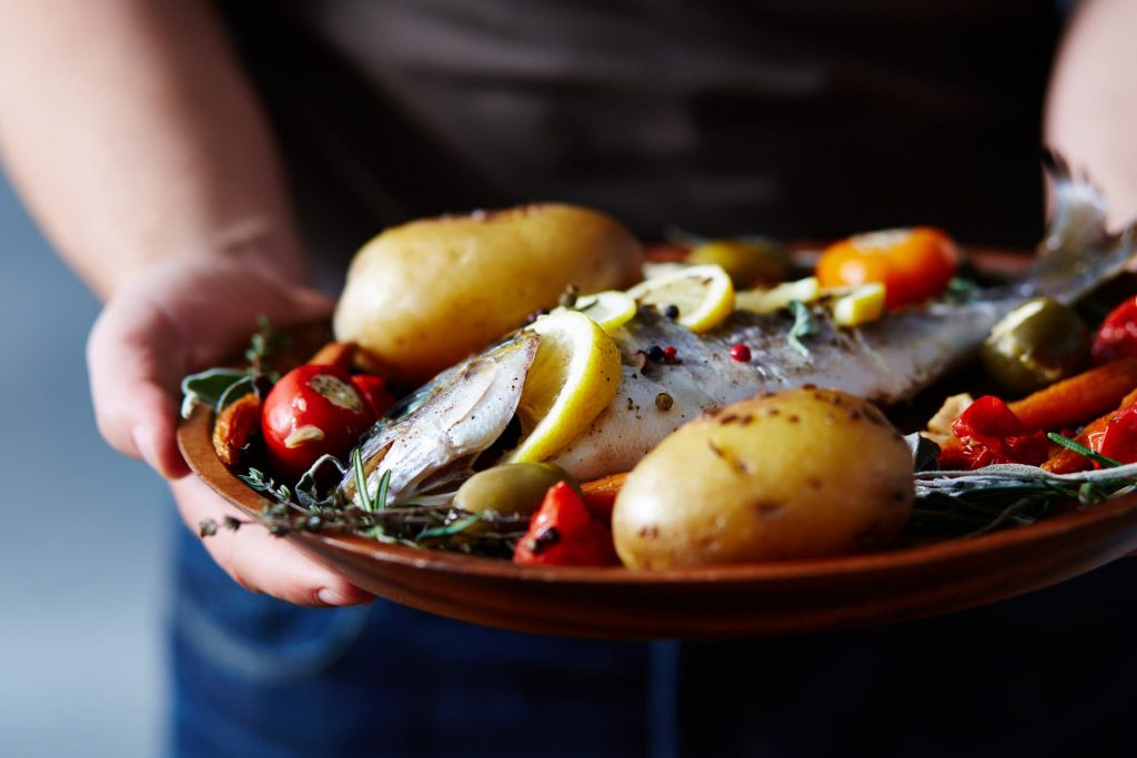 person-holding-plate-of-food-including-cooked-fish-potatoes-and-cherry-tomatoes-with-herbs