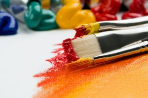 paintbrushes-with-orange-and-yellow-paint-laying-on-canvas-with-color-gradient