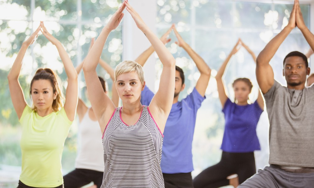 Adults perform yoga exercises at a YMCA location.