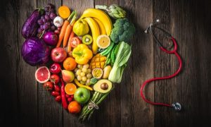 A heart-shaped table holds healthy foods to eat, including a colorful variety of fruits and vegetables.