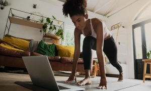 A woman does workouts at home on a floor pad while viewing a laptop