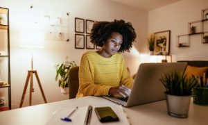 Young woman with dark curly hair and yellow sweater in D.C. apartment sitting in front of a laptop taking continuing education class.