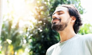 Dark-haired man with a beard practicing mindfulness exercises outdoors.